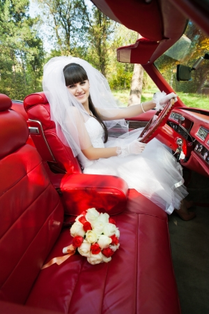 Bride driving convertible car with bouquet of flowers on front seat outdoors photo