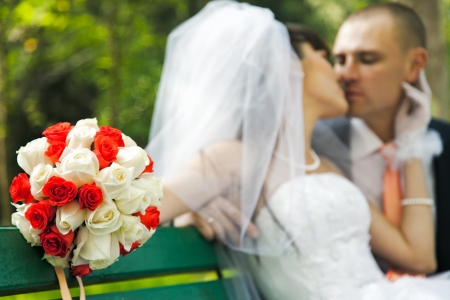 Closeup of bouquet of white and red roses with blurred bride kissing groom  photo