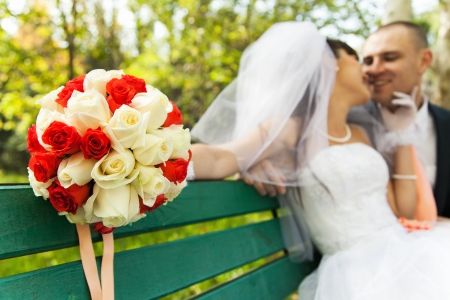 Bouquet of white and red roses with blurred bride kissing smiling groom photo