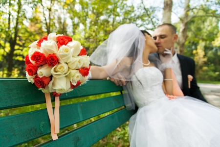 Bouquet of white and red roses with blurred bride kissing groom photo