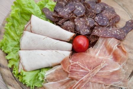 Meat plate with prosciutto and salad with selective focus Stock Photo