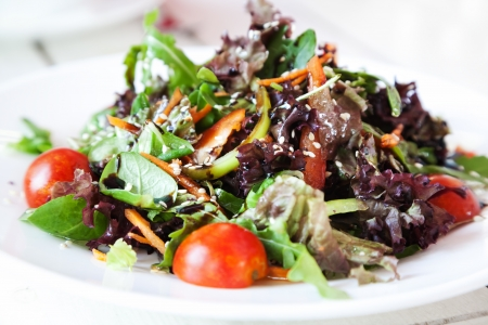 rocket lettuce: Fresh vegetable salad with arugula on white plate with selective focus Stock Photo