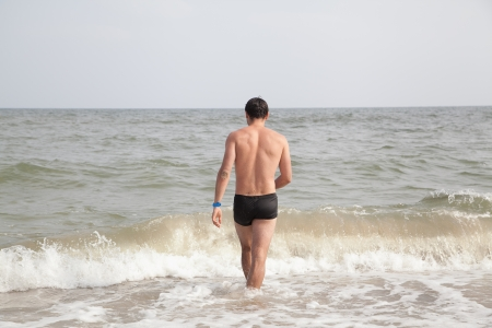 Young man with his back in shorts going to the sea with selective focus photo