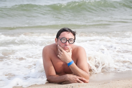 Geek in glasses posing on the beach with duckface and selective focus photo