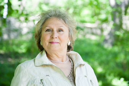 Positive senior aged woman outdoors in park