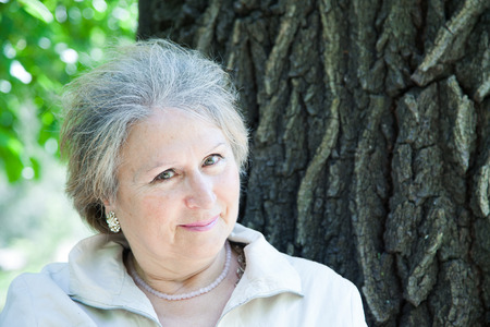 face in tree bark: Flirting senior aged woman outdoors next to a tree