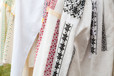 Row of white textile shirts with colored ethnic folk patterns  photo