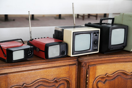 Row of portable vintage TV sets with selective focus photo