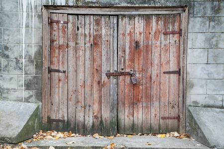 Old wooden barn door locked with padlock photo