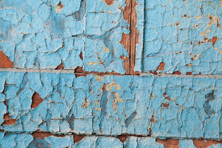 crackles: Peeling blue paint on wooden planks with selective focus