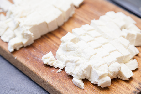 paneer: Closeup of paneer cut into pieces on cutting board Stock Photo