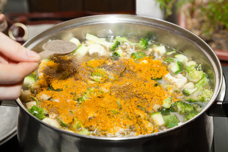 adding: Adding spices to vegetable soup