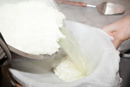 paneer: pouring paneer cheese in milk thrusting into gauze Stock Photo