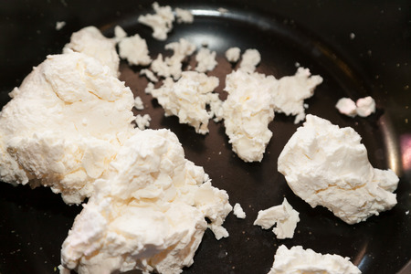 indian cookery: Pieces of cottage cheese on frying pan Stock Photo