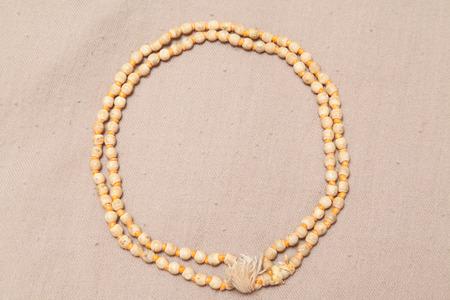 rolled japa mala chanting beads on woolen texture