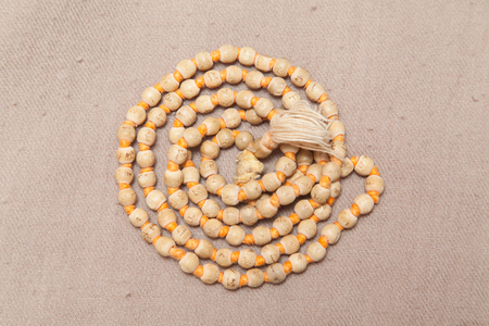 Closeup of rolled chanting beads on woolen texture Stock Photo