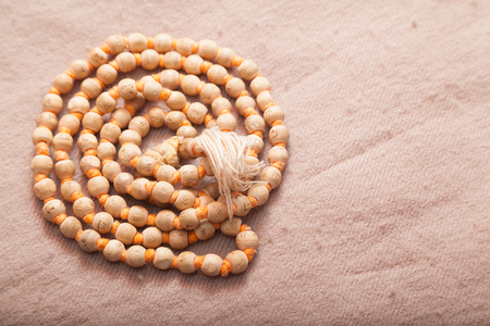 om sign: Closeup of rolled Indian japa mala chanting beads on woolen texture