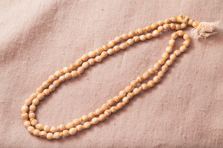 Traditional Indian japa mala chanting beads on woolen texture Stock Photo