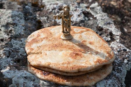 Offering food to statuette of Krishna 免版税图像