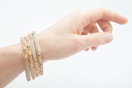 Female hand with set of golden bracelets on white background with selective focus