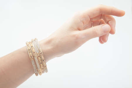 Side view of female hand with golden bracelets on white Standard-Bild