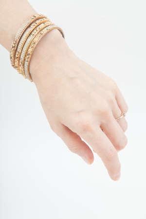 Female hand with set of golden bracelets on white background