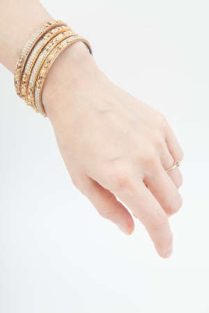 Female hand with set of golden bracelets on white background