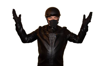 Isolated on white background man motorcyclist in a helmet and a mask from the coronavirus. The black jacket, protection and biker gloves Stock Photo