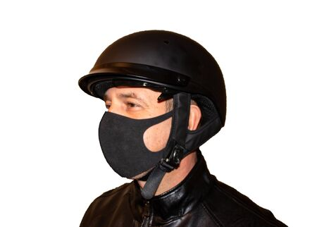 Isolated on white background man motorcyclist in a helmet and a mask that protects against coronavirus. Black jacket, protection and biker gloves