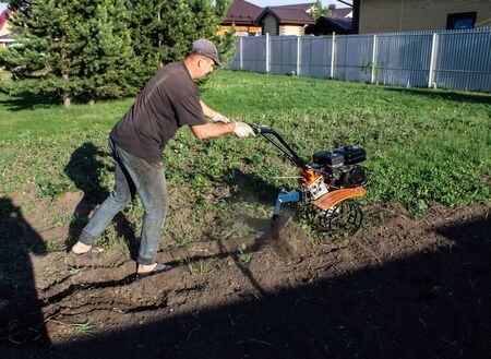 A man working in the field - dripping ground the motor-block with plow in working clothes