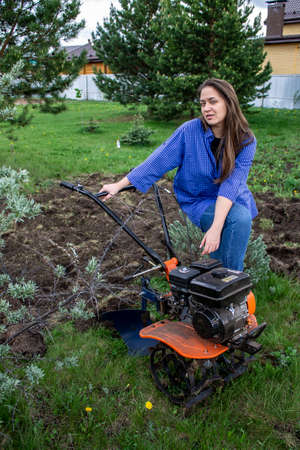 young woman in the garden with a walk-behind tractor
