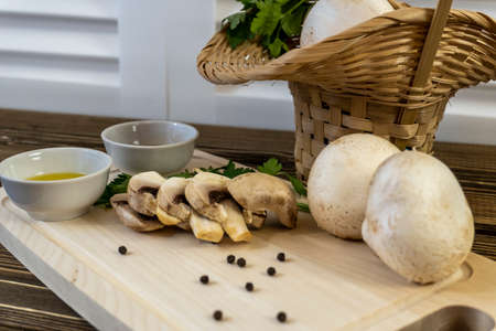Still life, Food photo of mushrooms champignons. Mushrooms are whole and chopped, basket with mushrooms. On wooden background