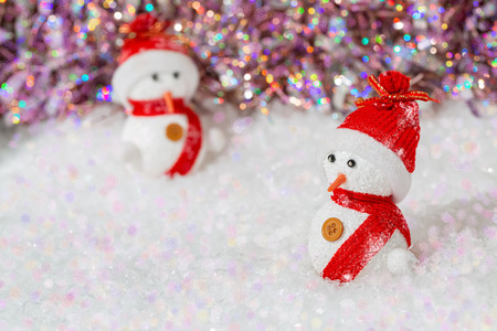 Christmas snowmen, on them red hats and scarves. Snowmen on white snow next to a colorful shining bokeh background. Greeting card. Happy Merry Christmas and New year. Copy space.Shallow depth of field Stok Fotoğraf