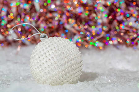 Christmas decoration.White ball with nacre pearls on a snow and beautiful blurred colorful background of glittering bokeh with glowing lights. Card. Happy Merry Christmas and New year. Art photography Stock Photo