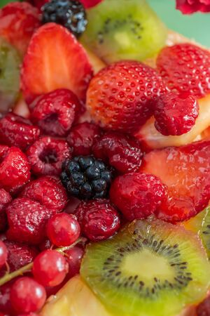 Fruits and berries in sweet gelatin on the cake. Background of strawberries, kiwi, currants, raspberry, pineapple, blackberry. Delicious dessert. Soft focus. Closeup. Top view.