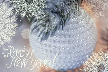 New Year Holiday greeting card. White ball with nacre pearls, pine branches and a garland in the snow. Shallow depth of field. Toned image. Blurred bokeh background. Snowflakes. Words