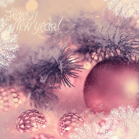 Happy New Year Holiday greeting postcard. Beautiful copper ball, pine branches and a garland in the snow. Snowflakes. Blurred bokeh background. Shallow depth of field. Toned image. Copy space.