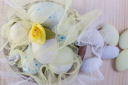 Easter sweet eggs or candies on a white transparent cloth and yellow flower on a wooden table. Decoration for the holiday. Shallow depth of field. Eggs on a white fine silk. Toned image. Closeup. Reklamní fotografie