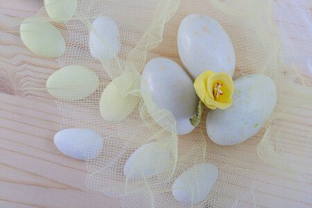 Chocolate eggs in white icing and yellow flower. Easter sweet eggs or candies on a white transparent light tulle. Decoration for the holiday. Shallow depth of field. Blurred background. Closeup. Reklamní fotografie