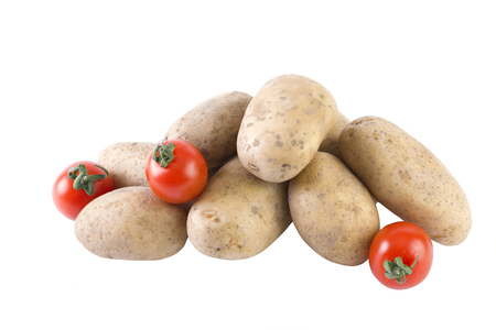 Potatoes and tomatoes on a white background. Potatoes on a white background. Red tomatoes with potatoes. Stock Photo