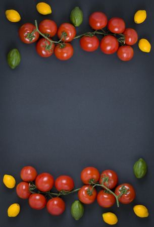 Red tomatoes with lemons on a black background. Composition from vegetables on a black background.