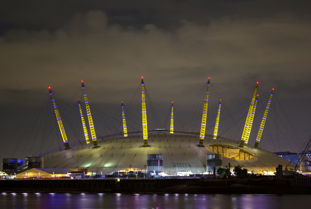 o2: The night illumination of the Millennium Dome, also called O2 Arena, in the distance across the river Thames during the Olympic Games time in London Editorial