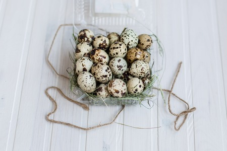 Quail eggs in a transparent plastic container on wooden background