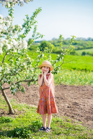 charming little baby girl in a blooming spring garden