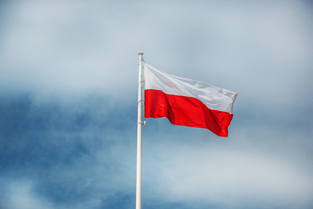 Polish national flag and blue spring sky
