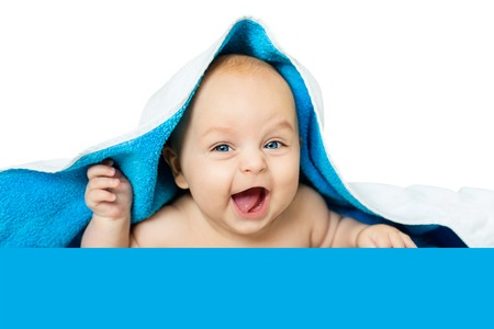 cute baby with big eyes under a blue towel on white, isolated. Stock Photo