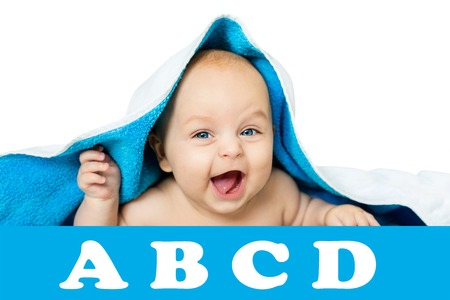 cute baby with big eyes under a blue towel on white, isolated. the child lies on a soft blanket