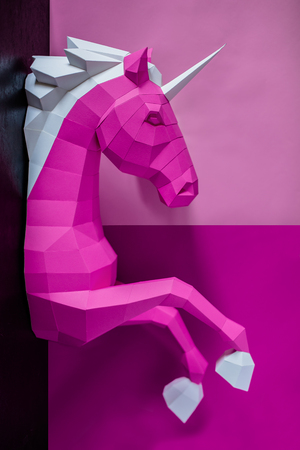 Head of a unicorn of paper on a pink and blue background.
