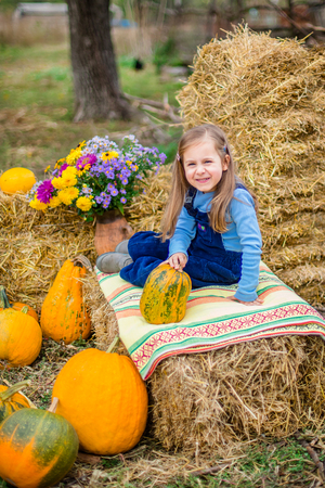 Funny kids in the background of hay with pumpkins.