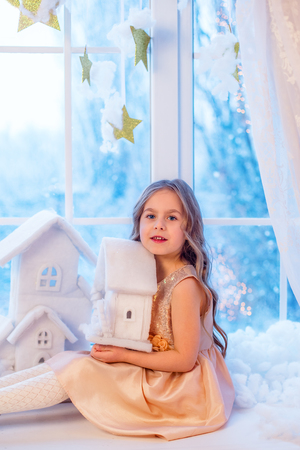 Cute little girl with curly hair at the window in anticipation of Christmas and New Years magic